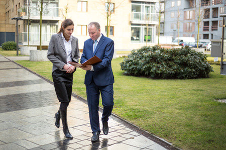 Two business people walking and discussing outside the office