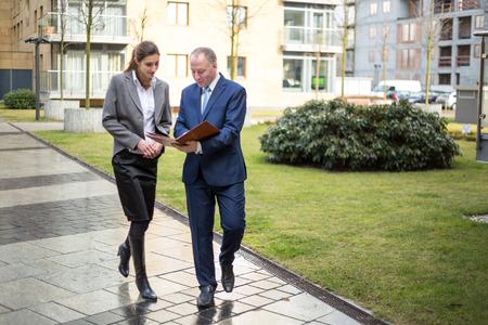 dos personas hablando: Dos hombres de negocios a pie y en discusiones fuera de la oficina
