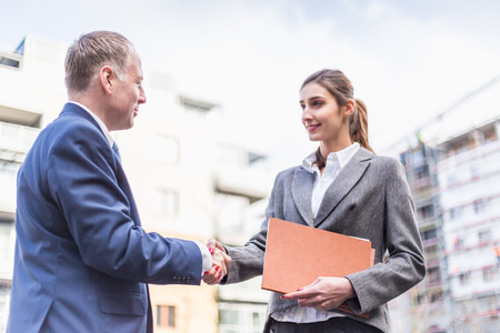 Businesswoman and businessman make a deal in front of offices.