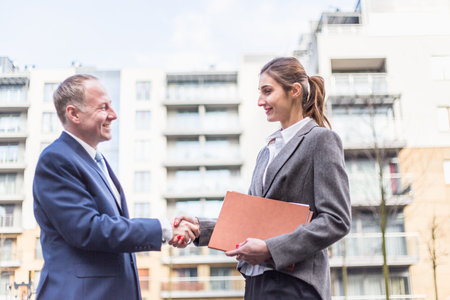 deal in: Businesswoman and businessman make a deal in front of offices.
