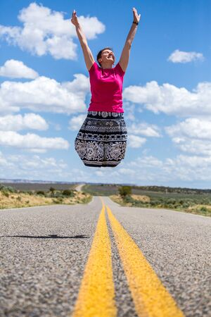 legless: Happy woman jumping over empty american road.
