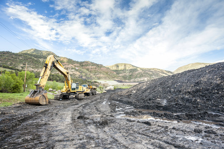 gold road: Mining machines, infrastructure and coal in mountainous mine Stock Photo