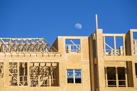 housing industry: Big multifamily housing under construction against blue sky