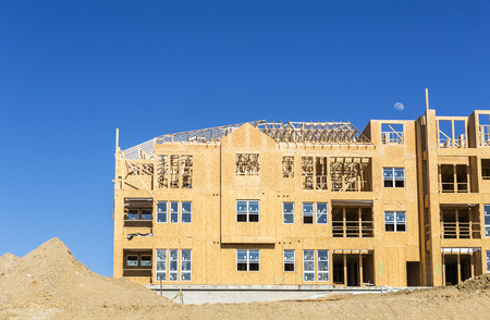 unfinished building: Big multifamily housing under construction against blue sky