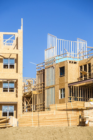 Big multifamily housing under construction against blue sky