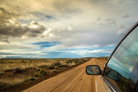 hombre manejando: Hombre sonriente que conduce a través de desierto en camino de tierra recta Foto de archivo