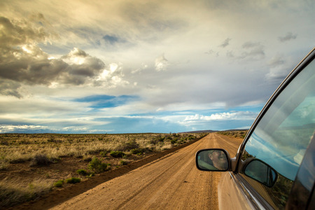 Smiling man driving through wilderness on straight dirt road Stockfoto