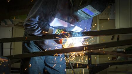 skilled labour: Man welding steel construction