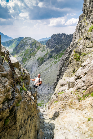 age 60: Middle aged man hiking and climbing in the Tatra mountains