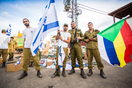 israeli flag: Mount Carmel, Israel - October 28, 2015: Israeli soldier with Israeli and Druze flag. Group of them was installing Israeli flag before bicycle race. Editorial