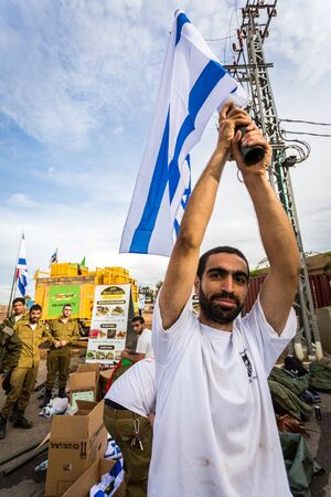 israeli flag: Mount Carmel, Israel - October 28, 2015: Israeli soldier with national flag. Group of them was installing Israeli flag before bicycle race. Editorial