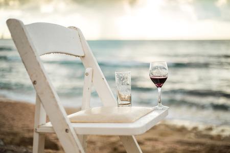 vaso de agua: Silla blanca con la copa en una playa de la izquierda despu�s de banquete de bodas