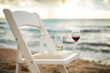 glass table: White chair with wineglass on a beach left after wedding banquet Stock Photo
