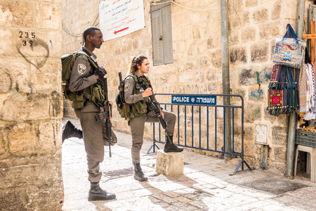 Jerusalem, Israel - November 3, 2015: Israeli soldiers - man and woman - guarding one of the mai street in old city