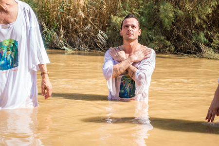 baptize: Jericho, Israel - November 2, 2015: Organised baptism for group of pilgrims in river of Jordan, the place which is believed that Jesus was baptized Editorial
