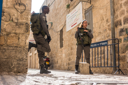 guarding: Jerusalem, Israel - November 3, 2015: Israeli soldiers - man and woman - guarding one of the mai street in old city