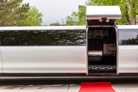 open up: White luxury limousine with open up door and red carpet leading to.