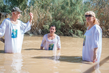 baptized: Jericho, Israel - November 2, 2015: Organized baptism for group of pilgrims in river of Jordan, the place which is believed that Jesus was baptized