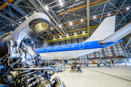 Refurbishment of white and blue airplane in a hangar. Stock Photo
