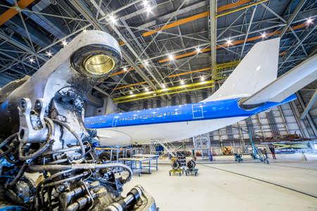 refurbishment: Refurbishment of white and blue airplane in a hangar. Stock Photo