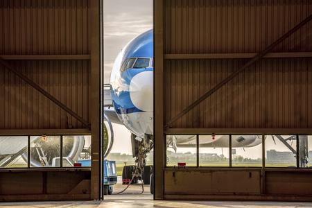aluminum airplane: Blue airplane in front of half opened door to hangar