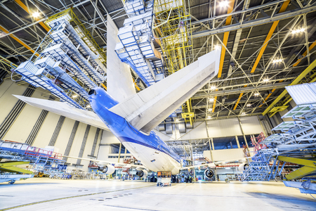 chassis: Refurbishment of white and blue airplane in a hangar. Stock Photo