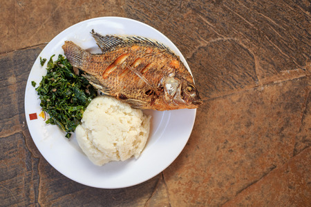 Traditional East African food - ugali, fish and greens in Kenya