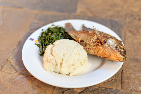 sorgo: Traditional East African food - ugali, fish and greens in Kenya