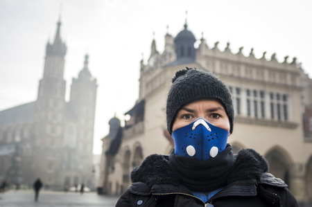 Woman using a mask, protecting herself from smog, Krakow, Poland Stock Photo