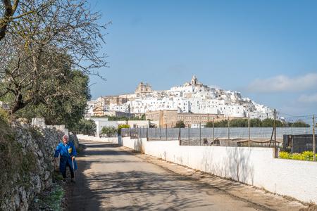 Ostuni, Italy -  February 27, 2017: Beautiful Ostuni with elderly man walking on the street