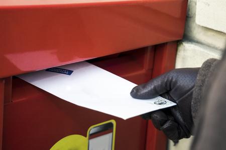 Envío de una carta. Colocándolo en la caja de correos roja Foto de archivo