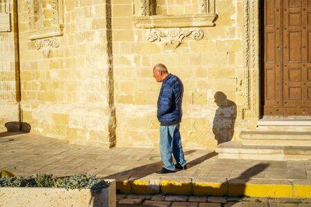 Gallipoli, Italy - March 3, 2017: Elderly man walking through sunny street of Italy Editorial