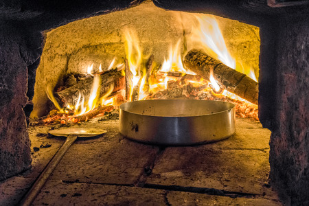 Delicious meal in pizza oven with firewood, Italy Stock Photo