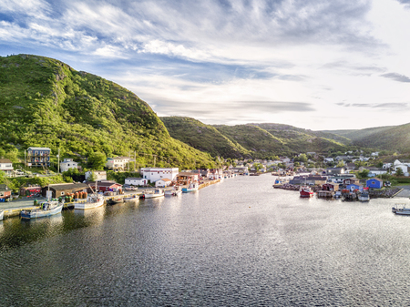 Charming Petty Harbour with green hills and colorful wooden architecture, Newfoundland, Canada
