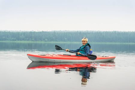 move in: Woman happy to paddle from red kayak on calm lake, Alberta, Canada