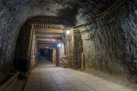 Exit from illuminated underground mine tunnel in salt mine in Bochnia, Poland