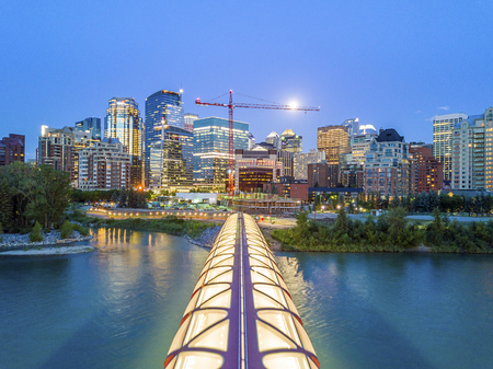 Calgary downtown with iluminated Peace Bridge and full moon, Alberta, Canada