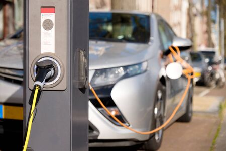 Charging modern silver electric car in public charging station