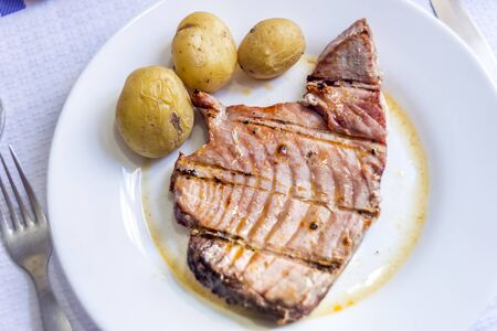 Juicy tuna steak with potatoes served on white plate