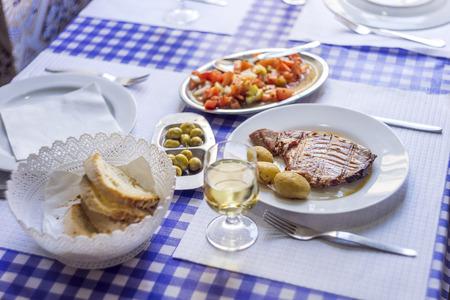 Tuna steak accompanied with potatoes, olives, tomato salad, bread and wine on white plate