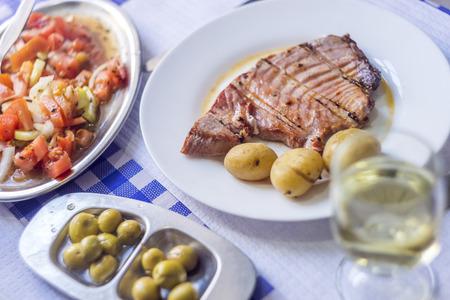 Tuna steak accompanied with potatoes, olives, tomato salad and wine on white plate