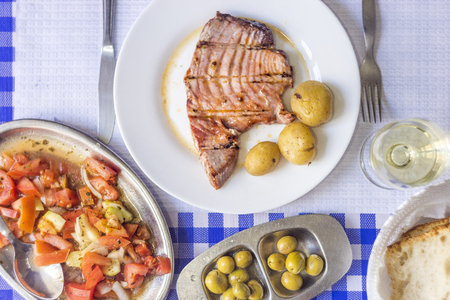 Tuna steak accompanied with potatoes, olives, tomato salad, bread and wine on white plate