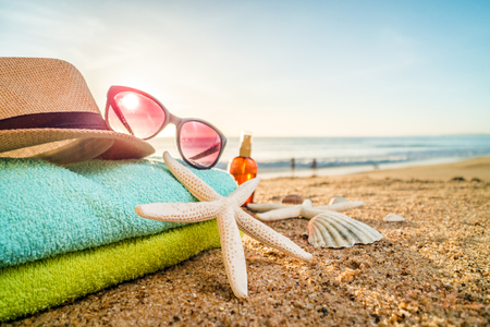 Summer accesories as sunglasses, towels, hat, sun block, shells and starfish on sandy beach in Portugal 版權商用圖片