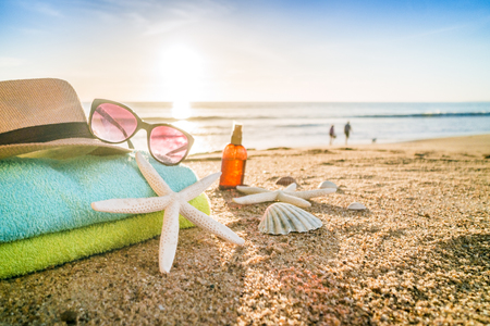 Summer accesories as sunglasses, towels, hat, sun block, shells and starfish on sandy beach in Portugal 写真素材