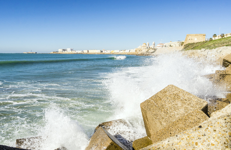 Atlantic waves breaking on the urbanized shore of old Cadiz, Andalusia, Spain