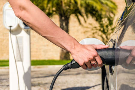 Woman plugs electric car to charging station in warm climate Stock Photo