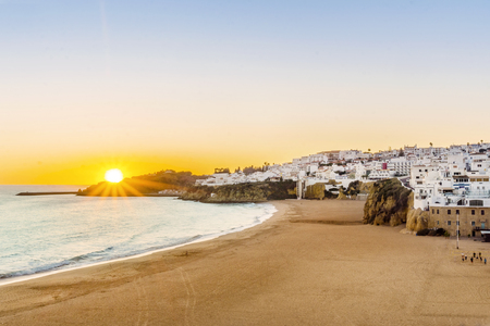 Sunset over beautiful cliffs between sandy beach and white architecture of Albufeira, Algarve, Portugal 版權商用圖片