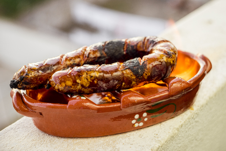 Traditional portuguese chourico or spanish chorizo prepared in a special clay pot on alcohol