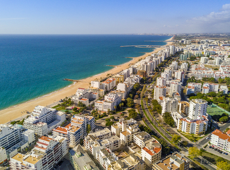 Wide sandy beach in touristic resorts of Quarteira and Vilamoura, Algarve, Portugal