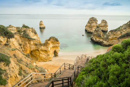 Beautiful Camilo Beach with wooden walkway descending to the sandy beach in Lagos, Algarve, Portugal Stock Photo